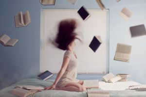 lady throwing books in air